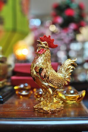 Golden Rooster with red comb figurine and ingots in the background usher lunar new year