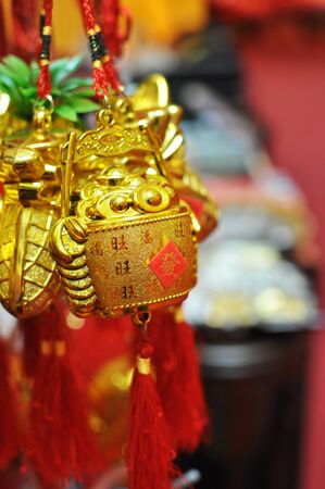 bucket of money: a bunch of gold bucket filled with ingots hanging on display, chinese text translation : prosperity