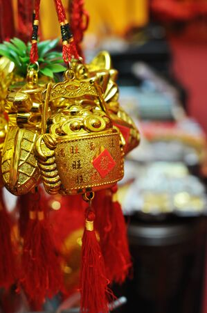Red strings tied to gold buckets filled with ingots hanging on display, chinese text translation : prosperity Stock Photo