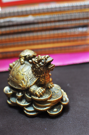 Dragon-turtle or tortoise with a small turtle shell on the stands on the coins - a symbol of prosperity and success in China. Metal copper.