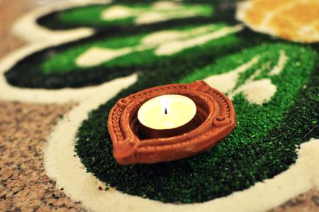 Hindu Deepavali Oil lamp placed Green kolam, floor art Stock Photo