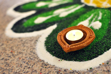 Traditional Oil lamp lit and placed on decorated Green kolam