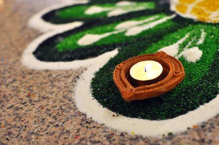 Hindu Deepavali Oil lamp lit and placed on decorated Green kolam