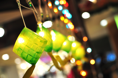 Colorful ketupat decorations with lights on and bokeh effect Stock Photo