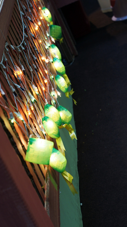 compressed rice: A row of green Ketupat Decorative Lightings for Hari Raya on a wooden panel