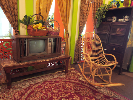 Antique box TV in living room of wooden house with rattan rocking chair in Malaysia village