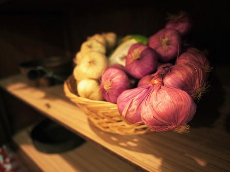 Onion shallots garlic in woven basket close up