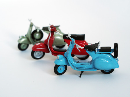 close up shot of three miniature model of motorbike, blue, green, red in a row