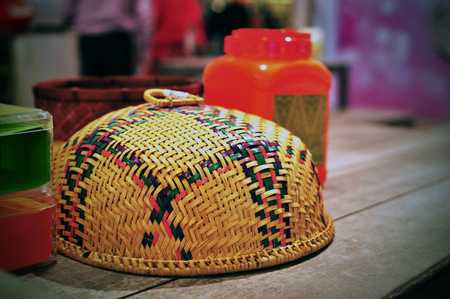 Food cover, handmade woven rattan, colourful, on kampung dining table
