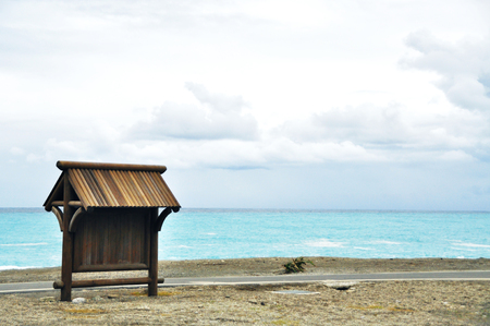 A wooden board with roof at seaside blue sky, calm sea, windy beach