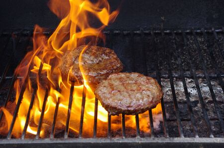 Hamburgers on a flaming BBQ Stock Photo
