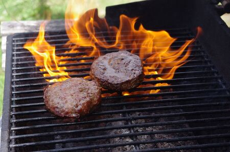 charbroiled: Hamburgers on a ring of fire BBQ Stock Photo
