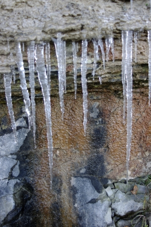 bumpy: Close up of a rock wall with icicles hanging on it