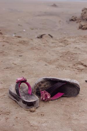 A pair of girls sandy flip flops at the beach photo