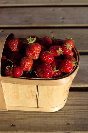 carreta madera: Una cesta llena de fresas en un carro de madera