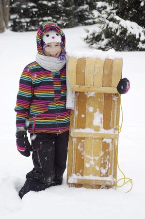 toboga: Ragazza con slittino di legno in piedi nella neve Archivio Fotografico