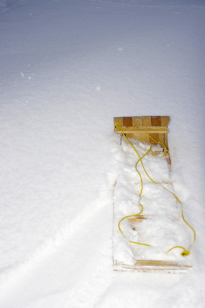toboggan: Wooden toboggan laying in snow