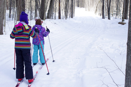 Girls Cross Country Skiing in woods