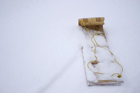 toboga: Slittino in legno posa in neve Archivio Fotografico