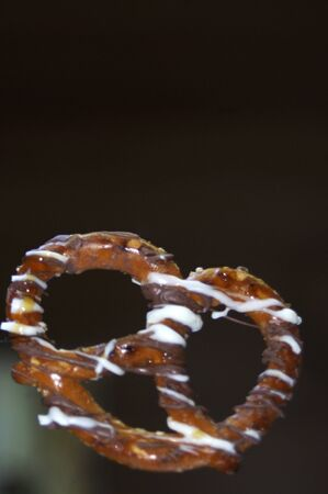 chocolate covered pretzel on black background