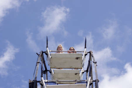 two wheel: two girls at top of Ferris wheel in a blue sky Stock Photo