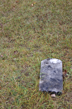 knocked over: gray old tombstone laying on grass