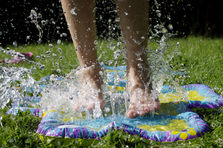 girl jumping into sprinkler