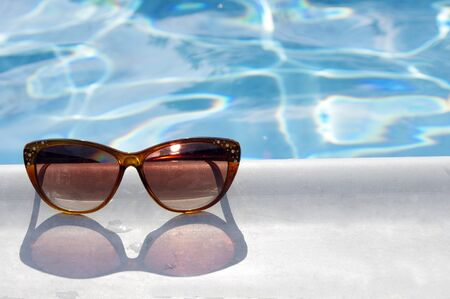 brown sunglasses by pool