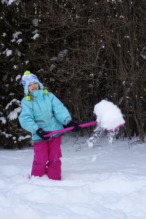 young girl shoveling snow Reklamní fotografie