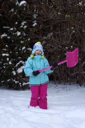 young girl with snow shovel