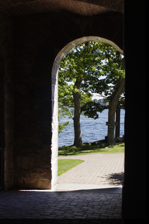 way out: arch way in shadow looking out to water