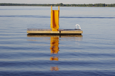 yellow waterslide on dock in smooth water Stock Photo