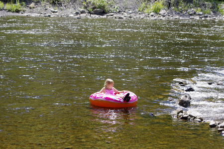 Girl with donut tube in river