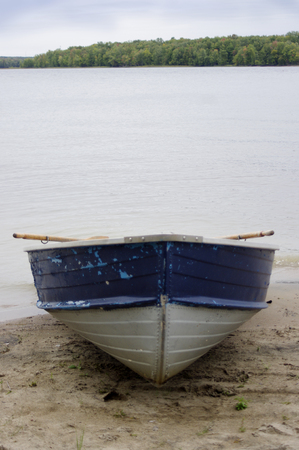 rustic blue boat on beach at river