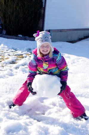 Girl carrying large heavy snowball
