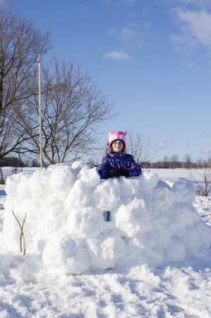Girl standing in large snow fort