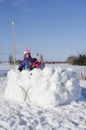 Girls standing in large snow fort Reklamní fotografie