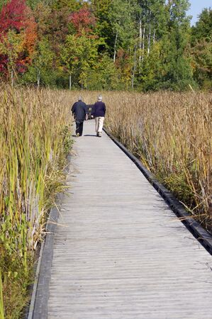 Two seniors walking on Wooden board walk with fall leaves