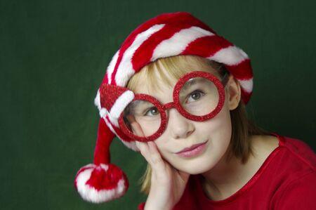 Girl with Santa glasses and Santa hat looking board Stock Photo
