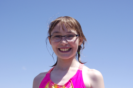 Pre-teen girl smiling in bathing suit