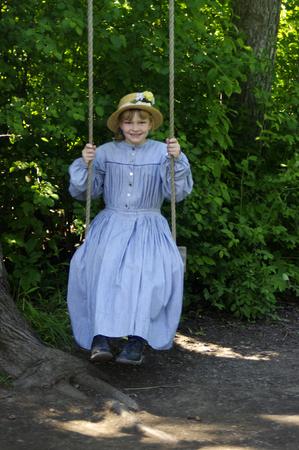 Girl dressed in vintage blue dress on tree swing