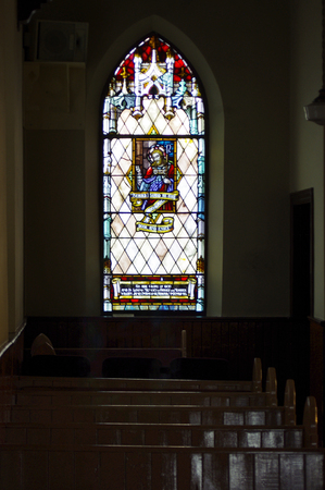 Stain glass window with wooden pews in dark church