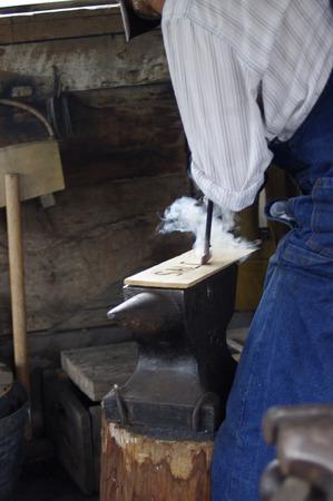 Man using vintage wood burning tools with smoke Imagens