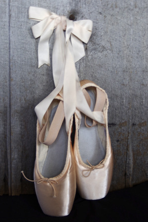 New pink ballet Pointe shoes on rustic wood  background