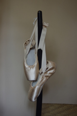 moody pink ballet Pointe shoes hanging on chair