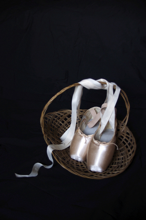 new pink ballet Pointe shoes in wood basket with copy space Imagens