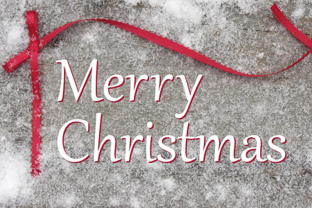 Merry Christmas words with red ribbon bow on snowy rustic board