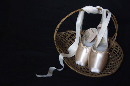 new pink ballet Pointe shoes in wood basket with copy space Stock Photo