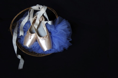 new pink Pointe ballet shoes basket with blue tutu  on black with copy space