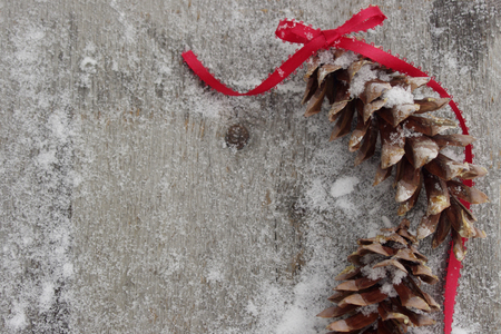 pinecone with red  ribbon on rustic wooden, snowy background with copy space
